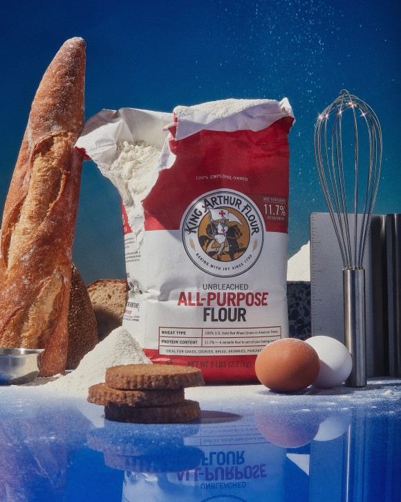A bag of King Arthur Flour propped up next to a baguette, eggs, and a whisk.